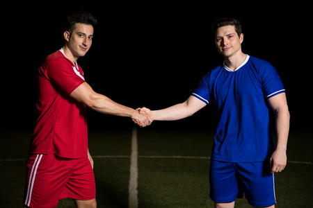Portrait of two soccer team captains shaking hands on field before starting a game