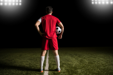 Full length of soccer player standing in red jersey on football pitch with ball