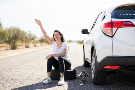 Woman with flat tyre on her car hailing oncoming traffic on country road for help Stock Photo