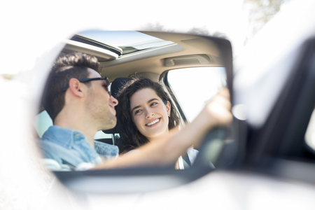 Wing mirror reflection of happy young man and woman looking at each other and smiling while driving car Stock Photo
