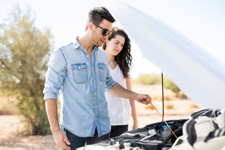 Young couple on the road trip having problems with their car