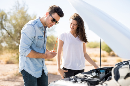 Caucasian couple on the road having problem with a car, guy checks the oil level with woman standing by