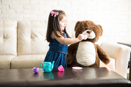 Pretty little girl playing with her teddy bear at tea party using child's tea set. Young girl child happily feeding her teddy bear in living room.