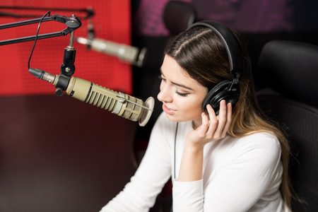 Close up good looking female radio announcer with headphones broadcasting through microphone in studio