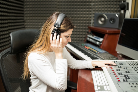 Young female composer listening her new track on headphone in recording studio