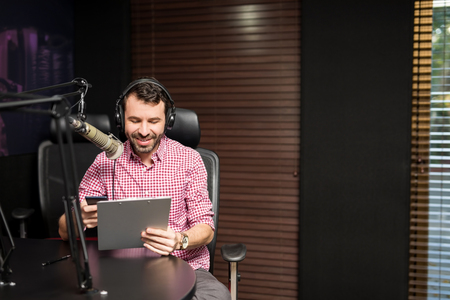 Radio host sitting with a clipboard and talking on microphone in studio