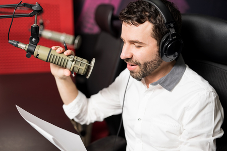 Close up good looking male radio host broadcasting through microphone in studio
