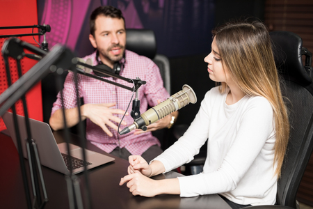 Young hispanic male and female host moderating a live radio show at radio station