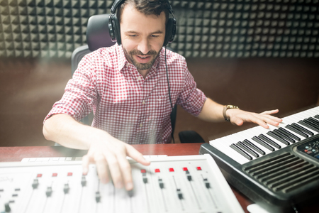 Latin male sound engineer adjusting control mixer in recording sound. Composing music with keyboard and audio mixer console.