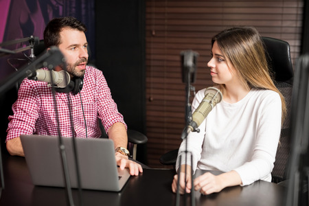 Portrait of male radio presenter interviewing a woman guest in a radio studio for a podcast