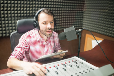 Handsome young man with beard hosting show live on radio station