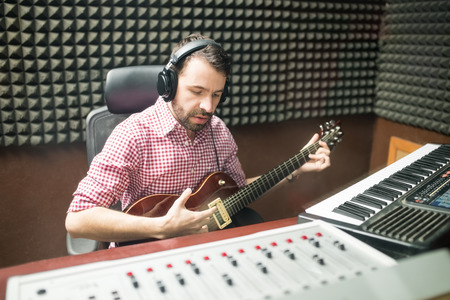 Handsome male hispanic guitarist in soundproof recording room playing guitar and composing music