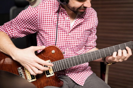 Close up of male artist playing guitar at radio station, broadcasting live music on air. Stock Photo