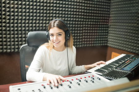 Portrait of confident young woman working in soundproof recording studio with sound mixing console and keyboard Stock Photo