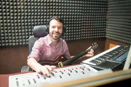 Portrait of hispanic young man with guitar working on a sound mixing console in soundproof recording studio