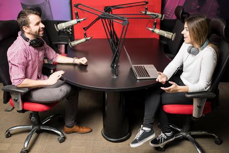 Een paar radiopresentatoren die met elkaar praten voor een radioshow in een studio