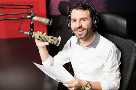 Portrait of handsome young male radio host walking at radio station with headphones and microphone