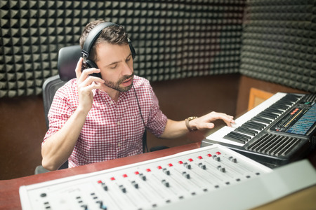 Hispanic sound engineer working with musical keyboard and mixing panel in the soundproof recording studio