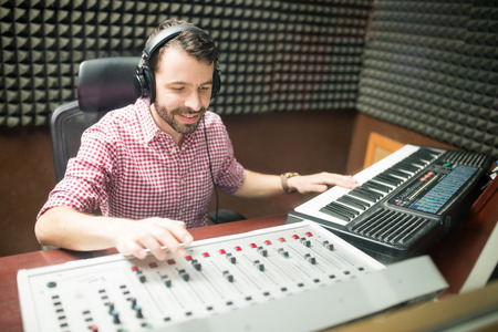 Handsome male musician with headphones in soundproof room composing music on mixer console and keyboard