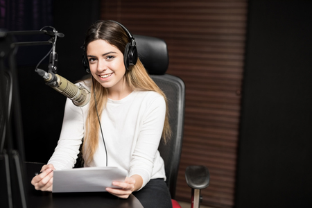 Portrait of beautiful young woman with headphones talking in mic at radio station Reklamní fotografie