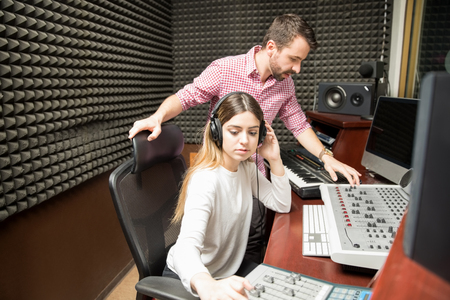 Couple of sound technicians working sound mixer console during live show