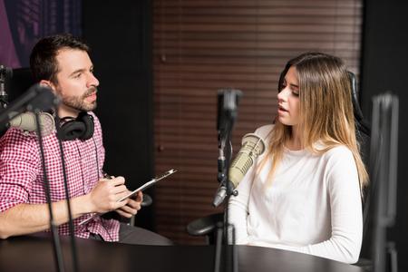 Podcasters hispanos de hombres y mujeres hablando entre ellos para radio podcast.