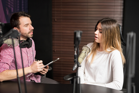 Hispanic man and woman podcasters talking with each other for radio podcast.
