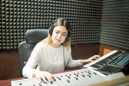 Female musician in soundproof room composing music on mixer console and keyboard Stock Photo