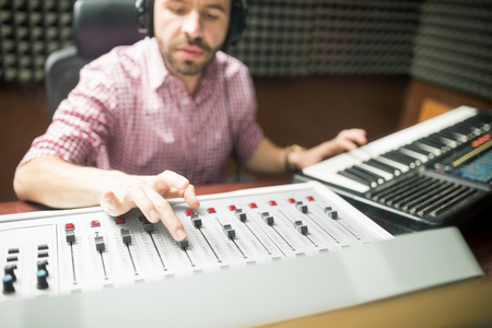 Male sound engineer hands working on sound mixer and keyboard for recording, broadcasting and music production in soundproof studio. Stock Photo