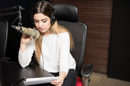 Woman working as radio announcer talking on microphone with a paper in hand, broadcasting a live show on air