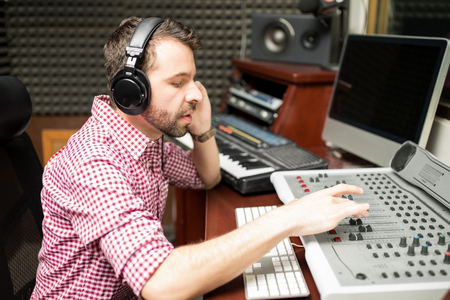 Hispanic male sound engineer working on audio mixing console in recording studio