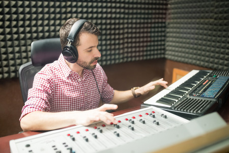 Musician wearing headphones preparing new music using keyboard and mixer console