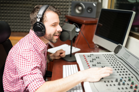 Handsome young radio announcer talking on microphone and adjusting the sounds on mixed console