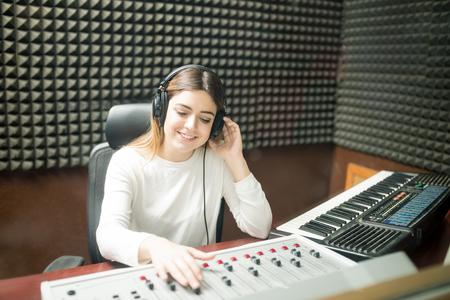 Beautiful female sound engineer wearing headphones working on sound mixer in soundproof recording studio. Stock Photo