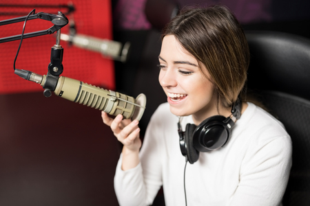 Confident female radio presenter talking into a mic in a radio station an smiling