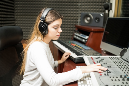 Side view of female sound engineer working with sound mixing panel and musical keyboard in the recording studio Reklamní fotografie