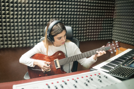 Woman with headphones playing guitar for preparing new sound track in soundproof recording room