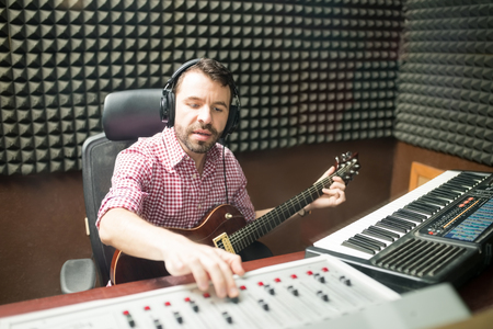 Hispanic male musician sitting with guitar and keyboard on table, fine tuning the sound on mixer console while composing music