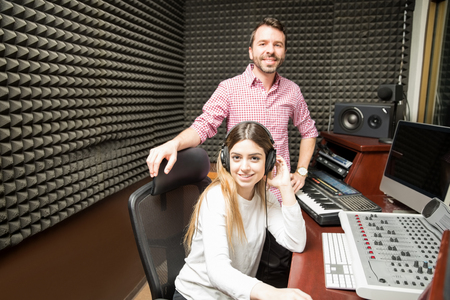 Portrait of experienced young sound technicians working in soundproof room making an eye contact Фото со стока - 98176330