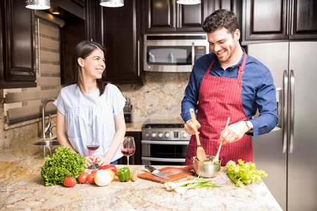 Smiling hispanic man mixing vegetables in bowl with his girlfriend standing by in kitchen at home