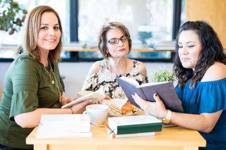 Portrait of attractive young hispanic woman with friends reading book at a book club Archivio Fotografico