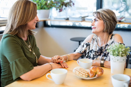 Pretty hispanic middle aged woman talking with her young daughter at cafe Stock Photo