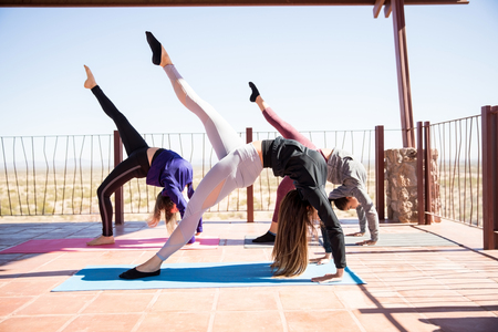 Three young women bending backwards with leg outstretched at yoga class Stock Photo