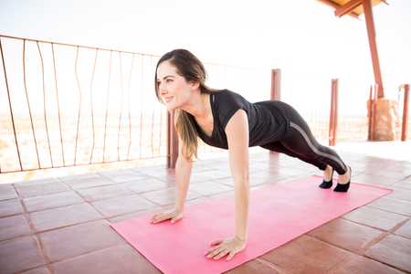 Portrait of strong woman doing yoga at fitness studio, holding plank pose. Stock Photo