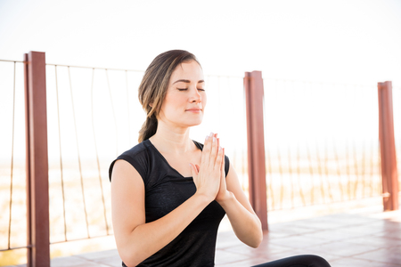 Portrait of beautiful young woman sitting in yoga meditation pose with her eyes closed and hands joined