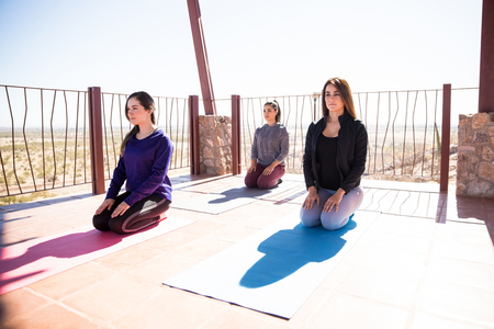 Healthy young women practicing meditation and yogic breathing exercises in yoga class