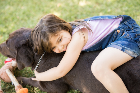 Cute girl in blue dungaree hugging best friend dog.