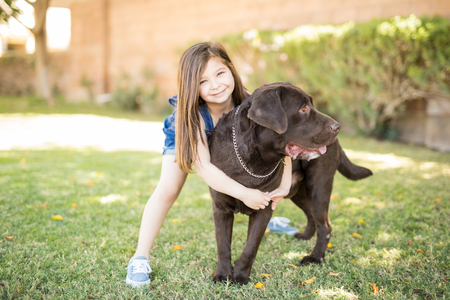 Smiling small child hugging chocolate labrador outside house.