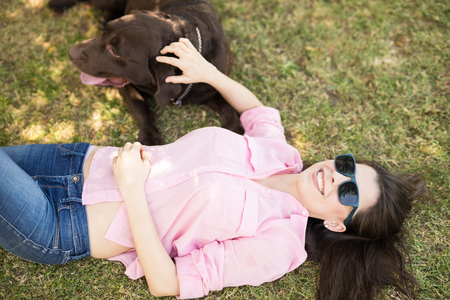 Cheerful woman in sunglasses with dog lying down on green spring time grass.