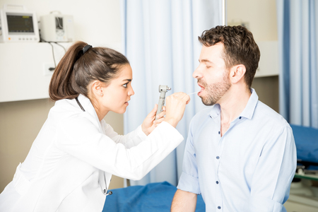 Professional young doctor using wooden stick and otoscope to examine throat of sick male patient